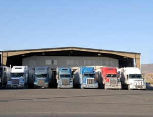 seven semi trucks at warehouse waiting to be loaded